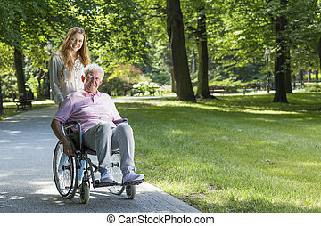 Woman with grandfather on a wheelchair in the park - Smiling...