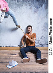 Woman's leg tied with line held by man sitting on the floor