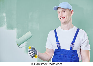 Man painting a wall - Young man holding a paint roller and...