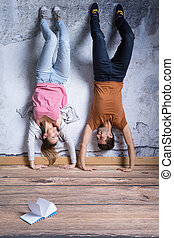 Smiled couple doing handstand in their room with book on the...