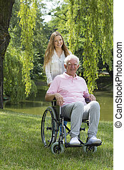 Woman with elderly man on a wheelchair
