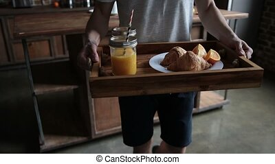 Man serving breakfast on wooden tray in bed - Close-up...