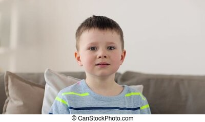 smiling little preteen boy at home - childhood, emotion,...