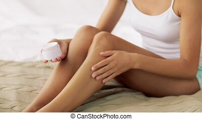 beautiful woman applying cream to her legs at home - people,...