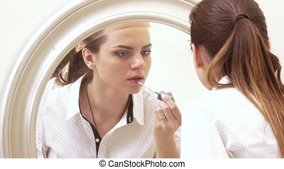 Girl paints face at mirror