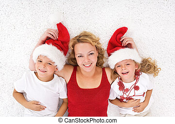 Woman and kids lating on the floor at christmas time
