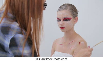7 shots. Professional make-up artist making body art in...