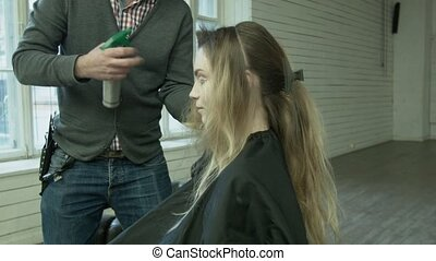A professional hairdresser makes a hairstyle for a young woman at the location. A male stylist moisturizes her hair with a sprinkler before cutting.