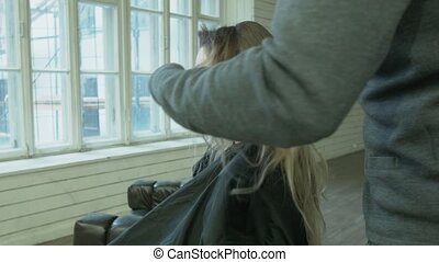 A professional male stylist makes a hairstyle for a young woman to shoot in advertising. The hairdresser combs the blond hair before going to the podium. Hairdressers in the workplace