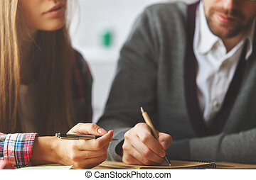 Attractive man and woman doing paperwork - Attractive...