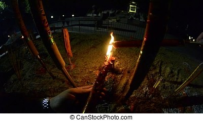 Burning candles in Buddhist temple at night. Men's hands on fire red large candles in the temple gopro. Red Candle in chinese temple. Fire first-person. Thai temple
