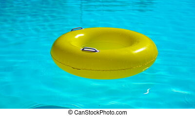 Swimming pool with a brightly yellow inflatable ring -...