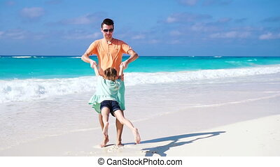Little girl and young father having fun during tropical beach vacation. SLOW MOTION.