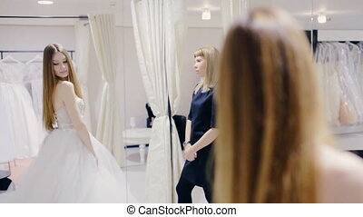 Pretty woman trying on wedding gown in fitting room - woman...