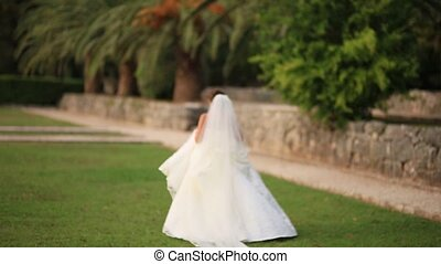 The bride runs along the grass in Milocer Park, in...