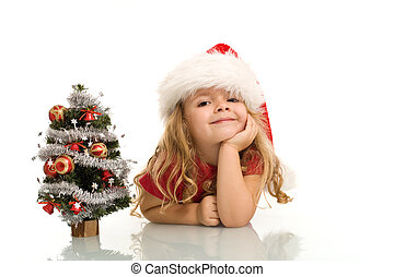Little girl with small christmas tree on the table dreaming...