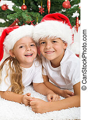 Happy kids in front of christmas tree laughing joyfully