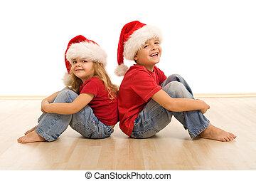 Happy kids on the floor wearing christmas hats