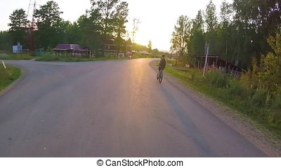Cyclist riding a bike on an open road to the sunset gopro. Ride on bike on the road. Sport and active life concept in the summer time first-person. Close up bike ride in the city at sunset. the Bicycle