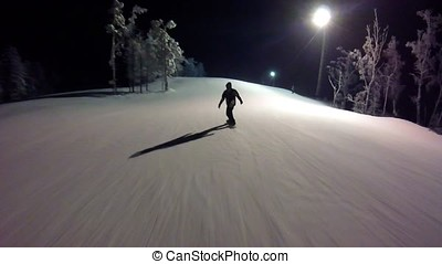 Male snowboarder slides down from the mountain in winter night. the guy on the snowboard is sliding from the mountain in the night gopro. Snowboarder skiing in high mountains gopro. first-person