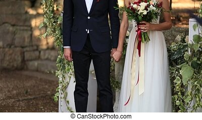 The newlyweds hold hands at the wedding ceremony. Couple...
