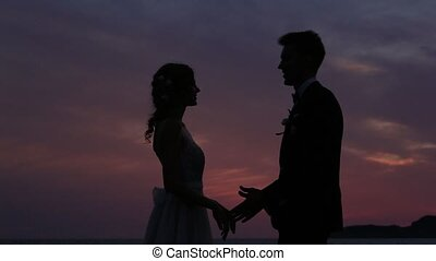 Silhouette of the newlyweds against the sky at sunset....