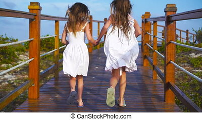 Little adorable girls on a wooden bridge running to the beach in luxury vacation