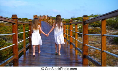 Little kids on a wooden bridge on their way to a white beach and turquoise ocean