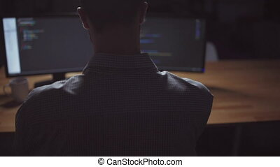 Rear view of freelancer programmer working at night - New...