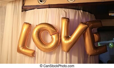 "The inscription ""Love"" from the golden balloons - The..."