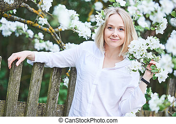 smiling adult woman with blossom in spring garden