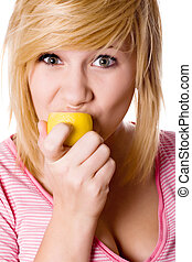 girl eating lemon - beautiful young girl eating lemon...