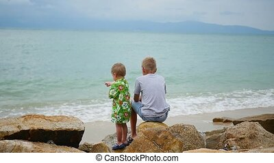 THAILAND. Children sit on the seashore and look out into the...