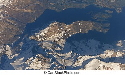 Flying above the Alps mountains and alpine towns in a valley...