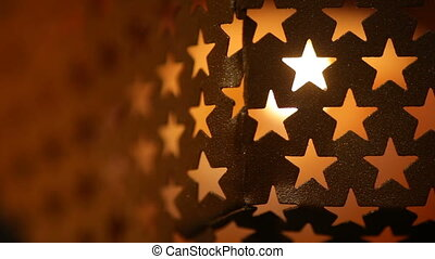 Abstract texture with star windows on a metal candlestick.