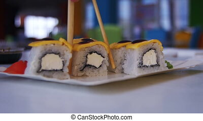 Woman with Chopsticks Takes Sushi from a Plate in a Japanese Restaurant