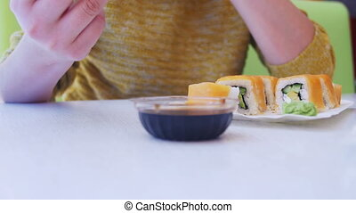 Woman with Chopsticks Eating Sushi from a Plate in a...