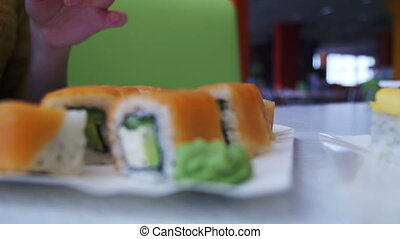 Woman with Chopsticks Takes Sushi from a Plate in a Japanese...