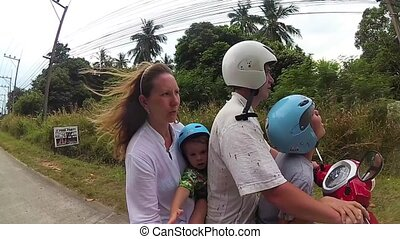 a happy family rides a motorbike in the tropics