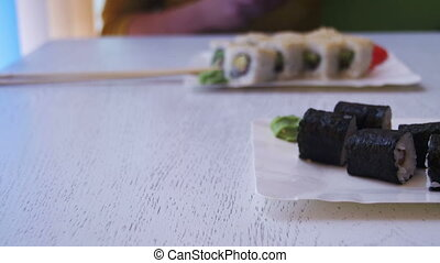 Plates of Sushi Rolls with Nori in a Japanese Restaurant on...