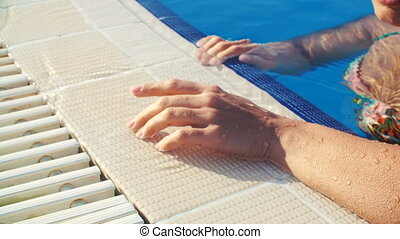 female hand on edge of pool on Sunny summer day closeup -...