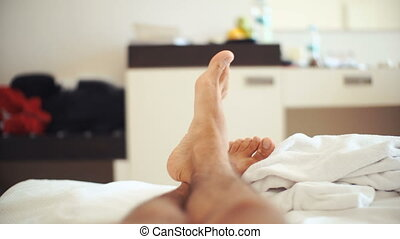 men's legs on bed in bedroom - men's legs on the bed in the...