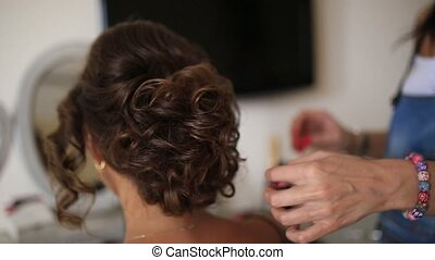 The hairdresser does the bride's hair. Professional at work....