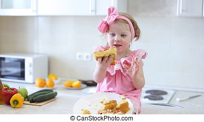 Cute Little Girl Eats Cake in The Kitchen.