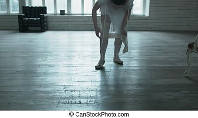 The dancer had a loose bandage on her leg. The young woman tied an elastic bandage and continued to dance on the wooden floor. Delicate dance of a girl in white.