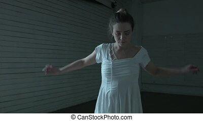 A young woman in white dances gently in the twilight. A beautiful girl in white clothes is dancing on a dark background in an old hall.