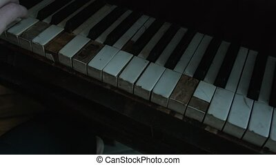 The broken keys of the old grand piano on which the musician...