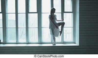 A beautiful young woman is standing against a large wooden window raising her high leg showing a stretching. A ballerina on the windowsill shows a reception with an extension.
