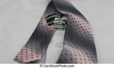 Dolly shot. Close-up knotted pink tie and cufflinks on a...