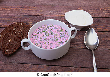 Popular spring cold soup okroshka with yoghurt. Okroshka in a bowl, sour cream and slices bread on wooden table. Selective focus